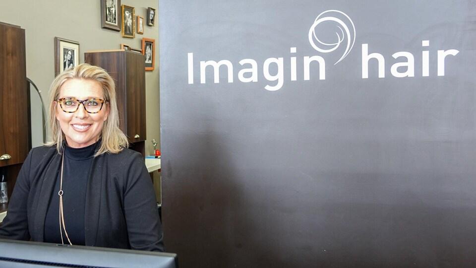 Sophie Cadorette, propriétaire du salon de Coiffure Imagine'Hair à Lévis derrière la caisse de son commercw