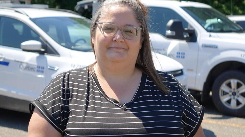 Une femme porte des lunettes et un chandail ligné.