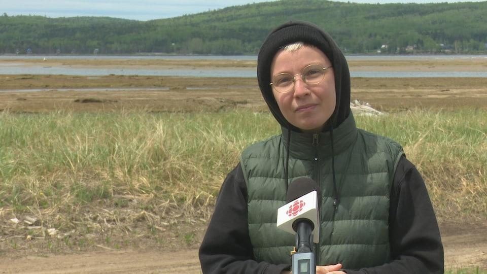 Sophie Jacquelin est debout devant un micro. On voit la plage derrière elle.
