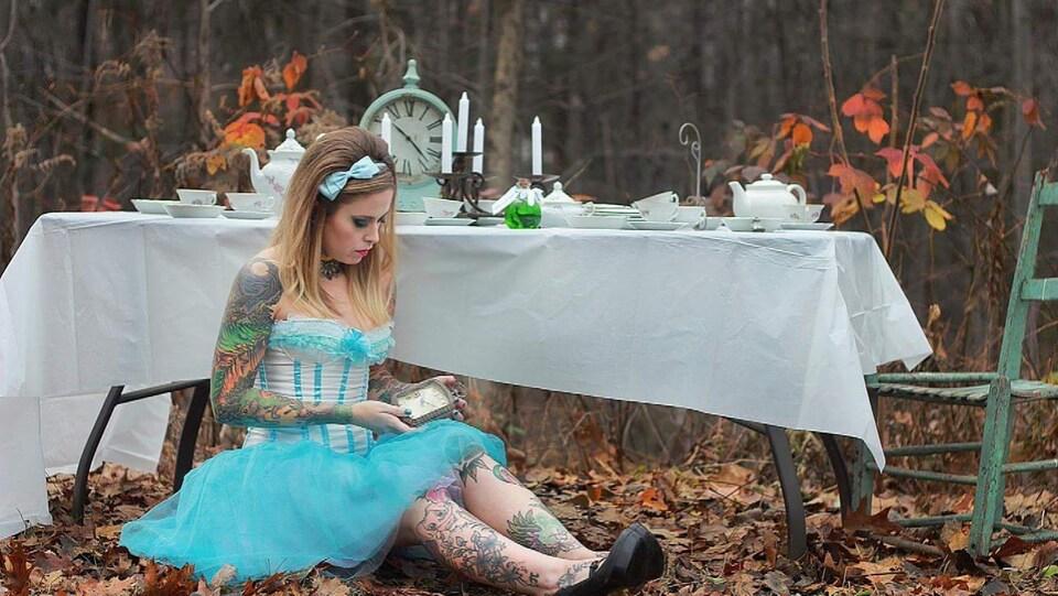 Une jeune femme porte une robe corset bleue claire à l'image d'Alice aux pays des merveilles. Elle est assise par terre. Ses bras et ses jambes sont tatoués. Le sol est recouvert de feuilles mortes.
