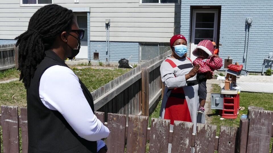 Sophie Wazilondeala avec son bébé, devant Elodie Furaha, de part et d'autre d'une clôture.