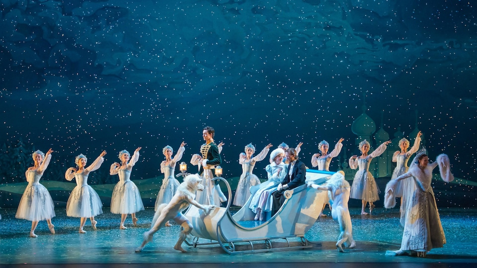 Un traineau blanc acceuille un homme et une femme qui sont entourés de danseurs célébrant la neige.