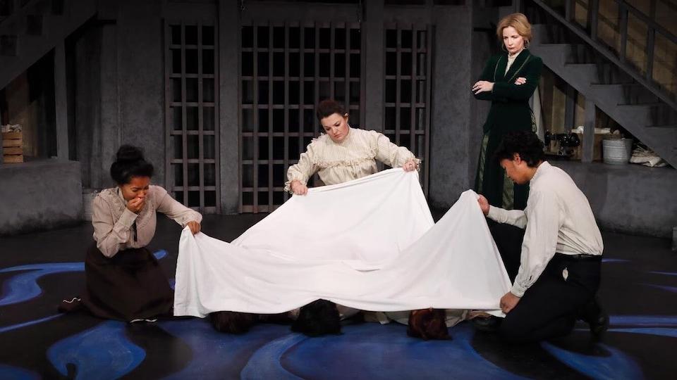 Des gens recouvrent des corps à l'aide d'un drap blanc