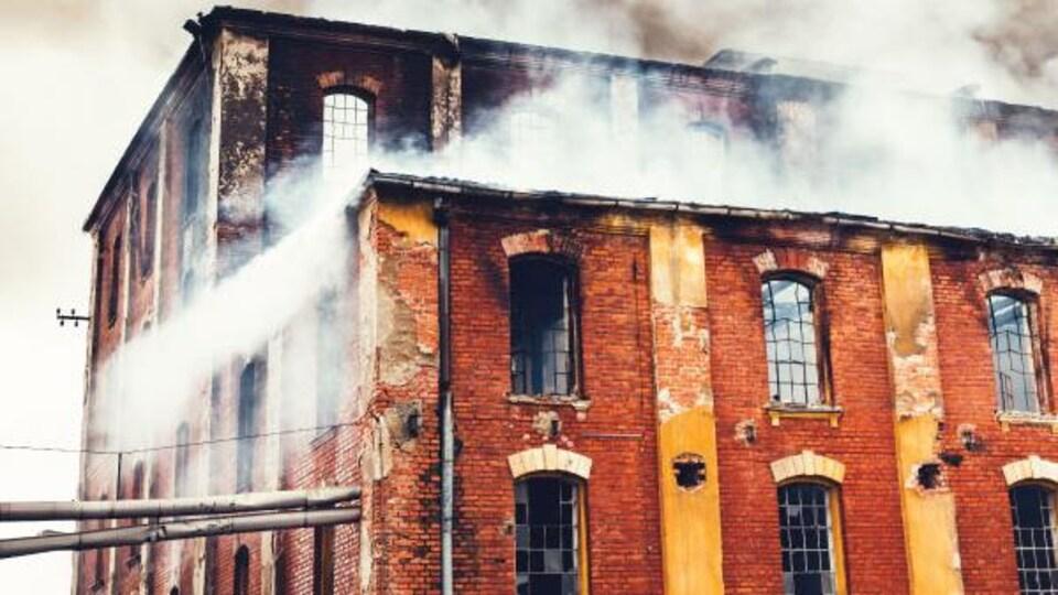 Affiche de la pièce qui montre un immeuble en fumée