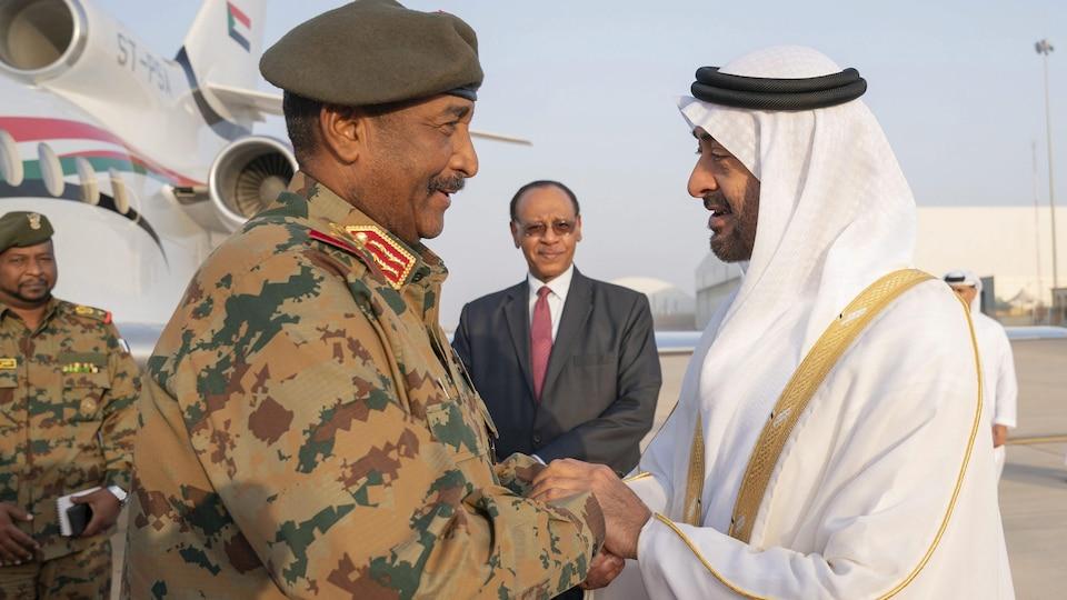 Abdel Fattah Al-Burhane serre la main de Mohammed ben Zayed sur un tarmac.
