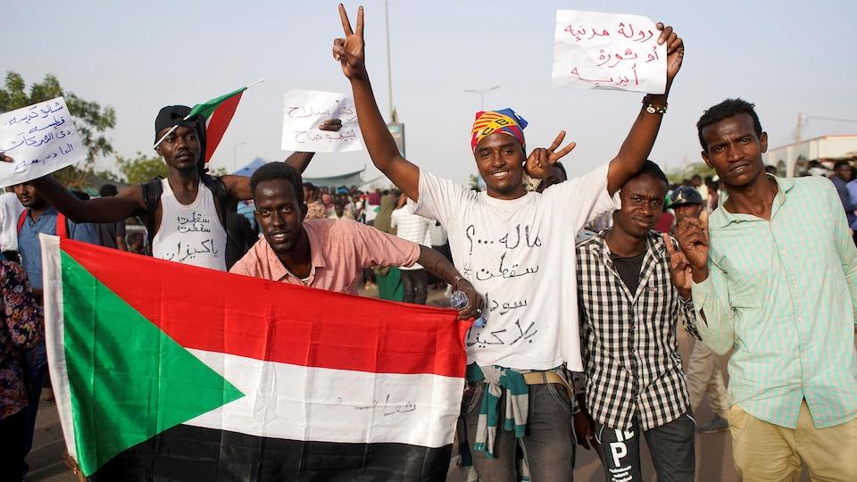 Des manifestants tiennent un drapeau soudanais dans la rue.