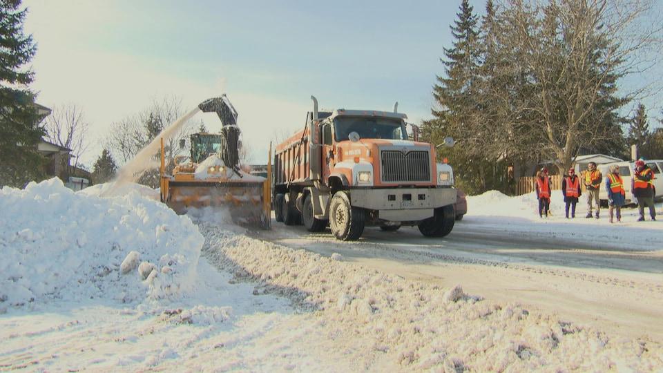 Une souffleuse et un camion ramassent de la neige à Gatineau.