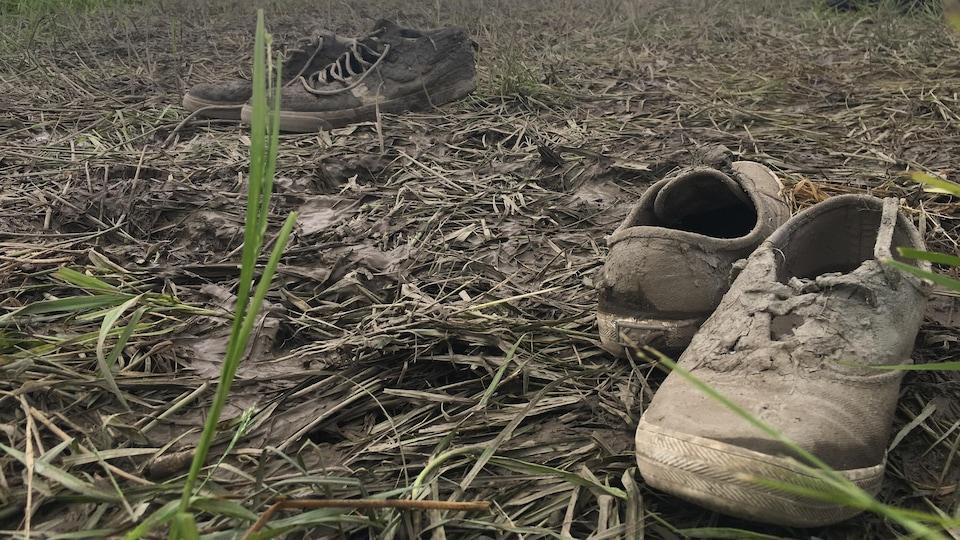 Deux paires de souliers boueux dans le gazon.
