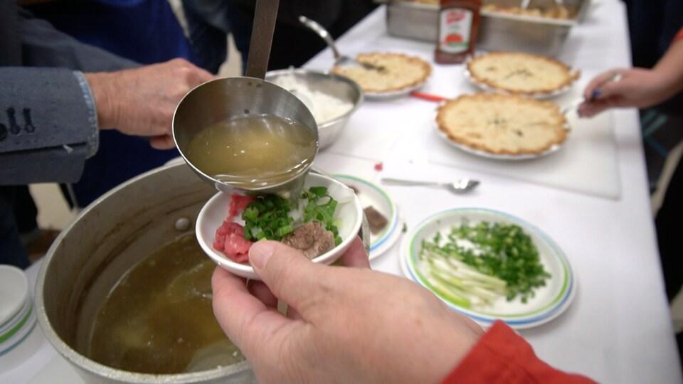 Une dame se sert une soupe.