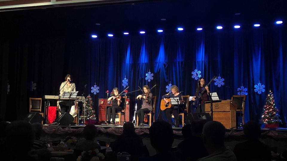 Cinq musiciennes jouent du piano, du violon, de la guitare et de la basse sur la scène.