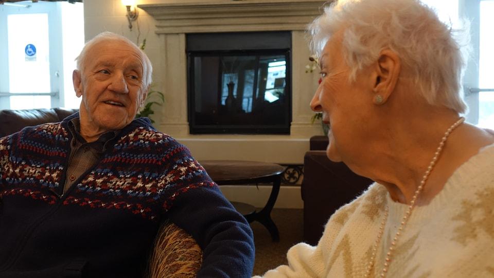 Un couple de personnes âgées de regardent en souriant.