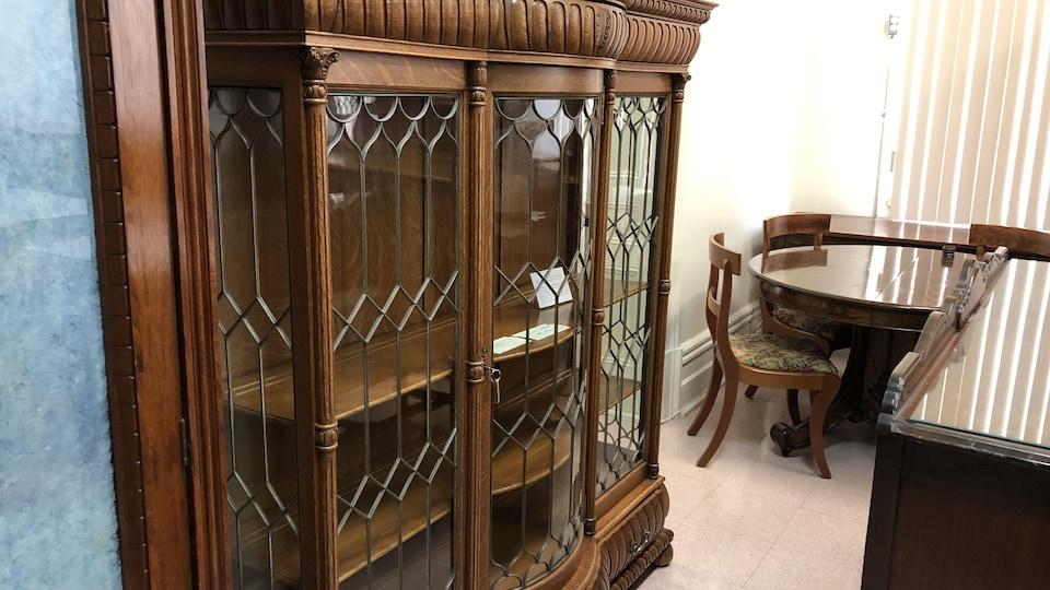 Une grosse armoire en bois vitrée et une table de cuisine sont en montre.