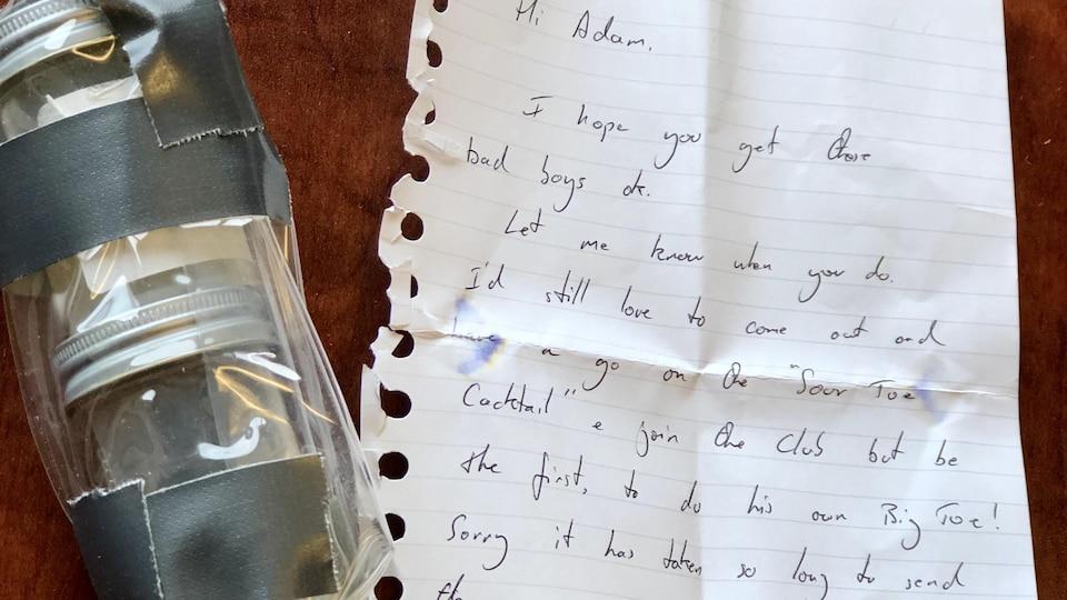 Une lettre accompagne des orteils dans une fiole contenant du liquide.