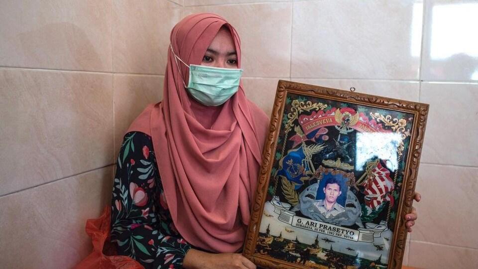 Une femme portant le voile et un masque chirurgical tient un cadre avec une photo d'un homme. Elle regarde vers le sol.