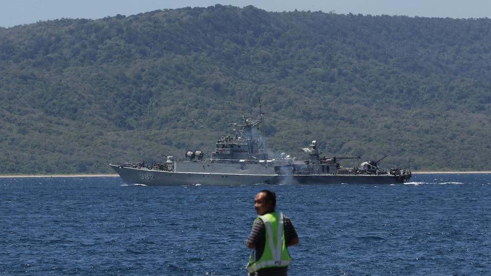 Un homme devant un navire militaire