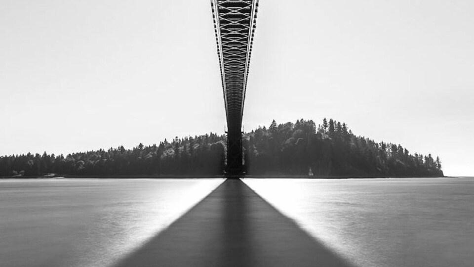 Photographie en noir et blanc du dessous d'un pont.