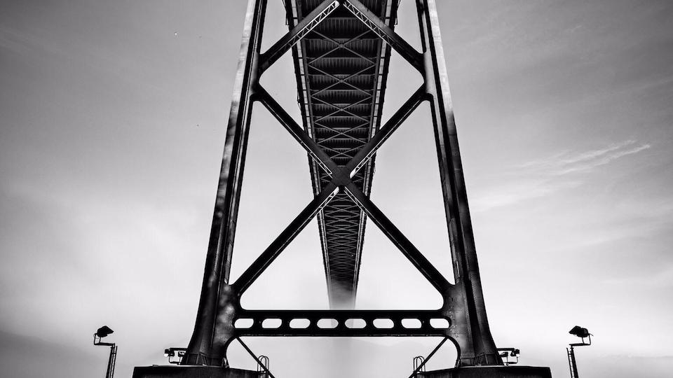 Photo en noir et blanc du dessous d'un pont.
