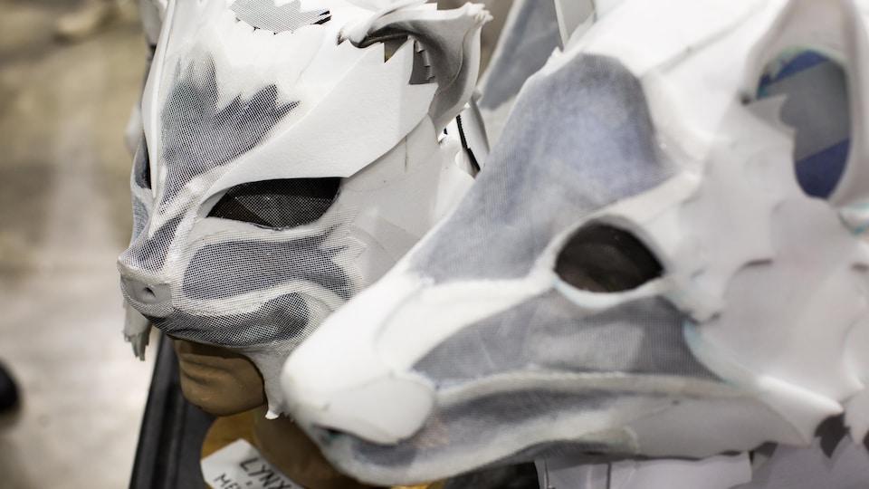 Un masque de lynx et un masque de loup inachevés sont en démonstration sur une table.
