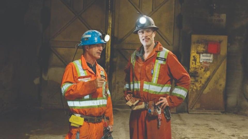 Deux hommes portant casques avec lumière et combinaison se parlent à l'intérieur d'une mine.