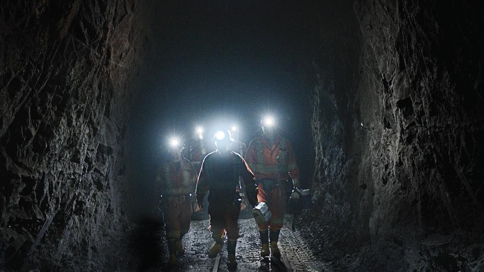 Cinq mineurs se promènent dans une mine, portant des casques équipés d'une lampe torche.