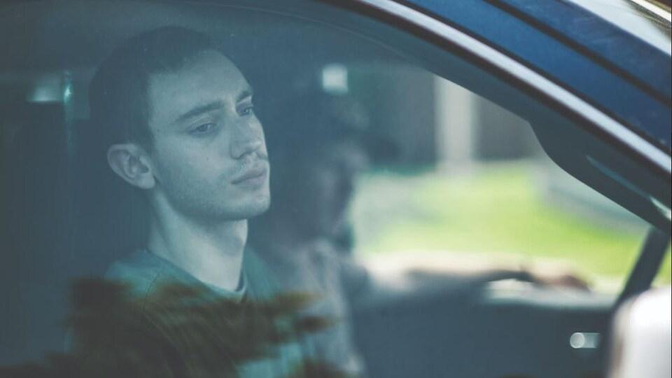 Un jeune homme assis du côté passager d'une voiture regarde vers la fenêtre d'un air triste.