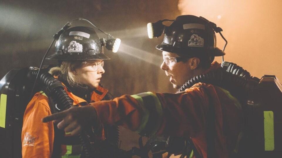 Une mineure et un mineur en combinaison de protection se parlent dans une mine.