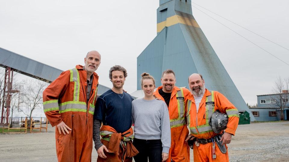 Des acteurs, dont James Hyndman et Michaël Gouin, posent en compagnie de Sophie Dupuis sur un site minier, habillés en mineurs.