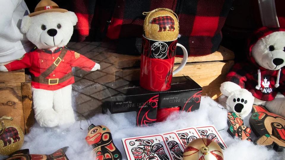 Un ours en peluche en habit de la police montée du Canada, un autre porte un chandail rouge avec une feuille d'érable et le mot Canada, une tasse, des cartes et des décorations de Noël inspirées d'art autochtone.