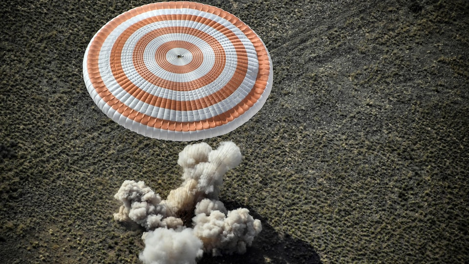 Un nuage de poussière s'élève de l'endroit où la capsule Soyouz a touché le sol.