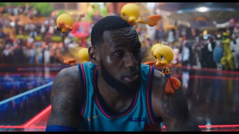 Un joueur de basket est assis alors que des petits oiseaux jaunes en dessins animés lui tourbillonnent autour de la tête.