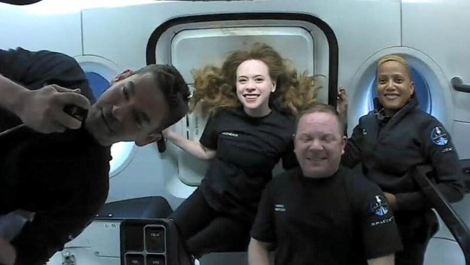 Les quatre membres de l'équipage, en apesanteur, sourient à la caméra.
