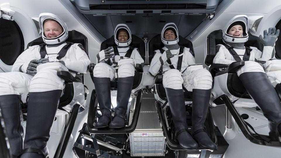 Quatre astronautes sont assis à l'intérieur d'une capsule spatiale.