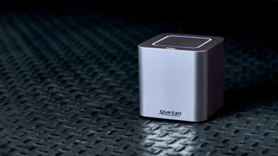 Un cube gris sur lequel il est écrit Spartan. Le dessus est illuminé. Le cube semble pouvoir tenir dans une main.