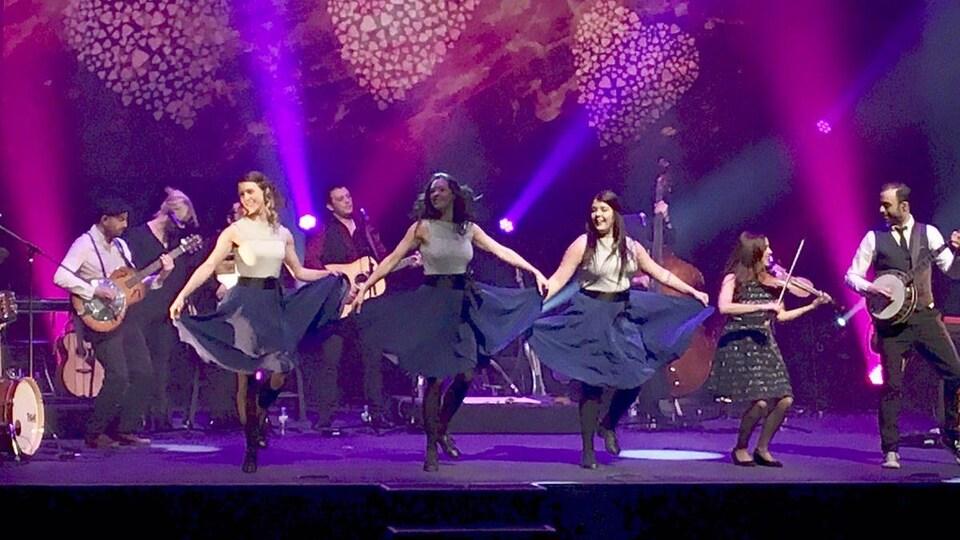 Des danseuses et musiciens sur une scène.