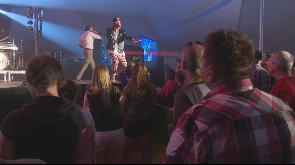 Deux chanteurs, micro à la main, devant une foule.