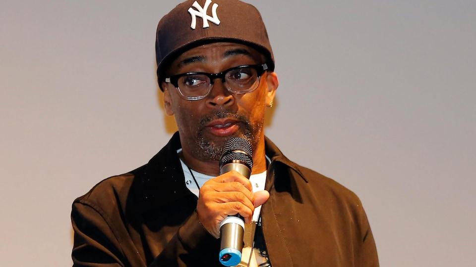 Un homme avec des lunettes et une casquette parle au micro.