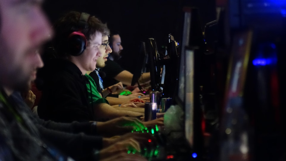 Plusieurs joueurs enlignés sur une longue table, regardant leur écran et les mains sur le clavier, jouant à un jeu vidéo lors d'une compétition.