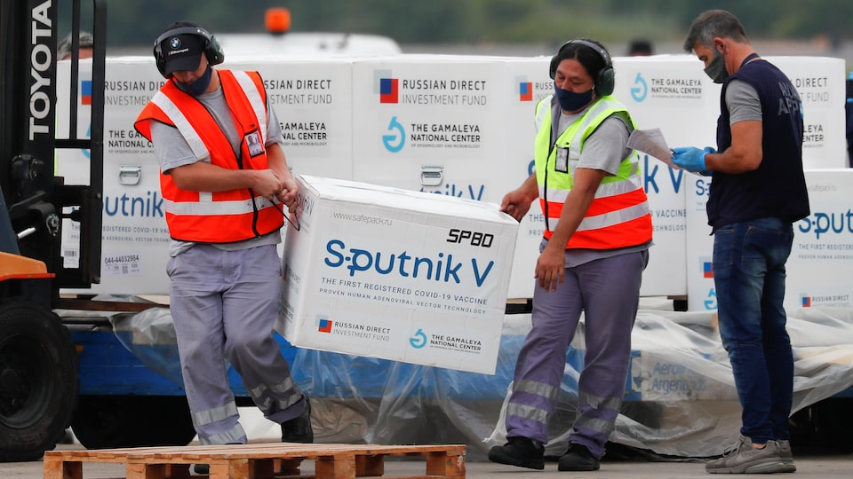 Deux personnes transportent une boîte du vaccin Spoutnik.