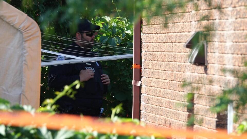Un policier examine un site sur le côté d'une maison.