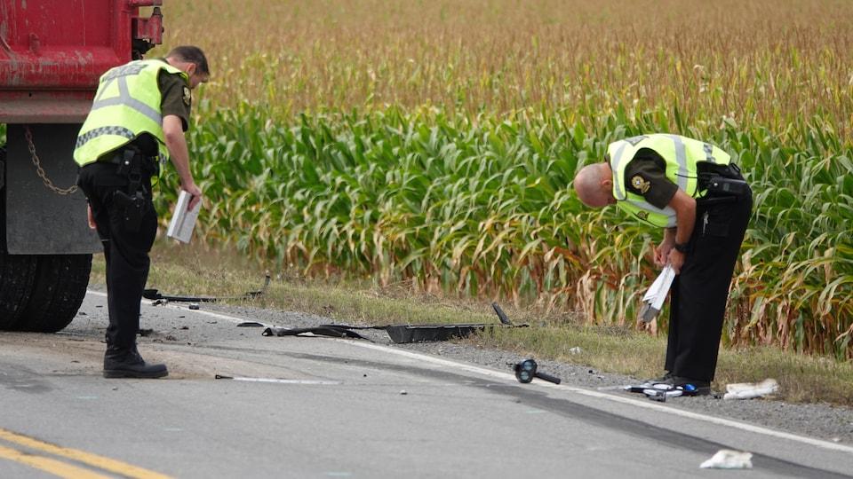 Deux enquêteurs prennent des notes sur la scène de l'accident.