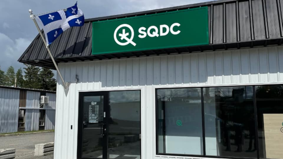 Bâtiment avec une porte d'entrée, la bannière de la SQDC et le drapeau du Québec.