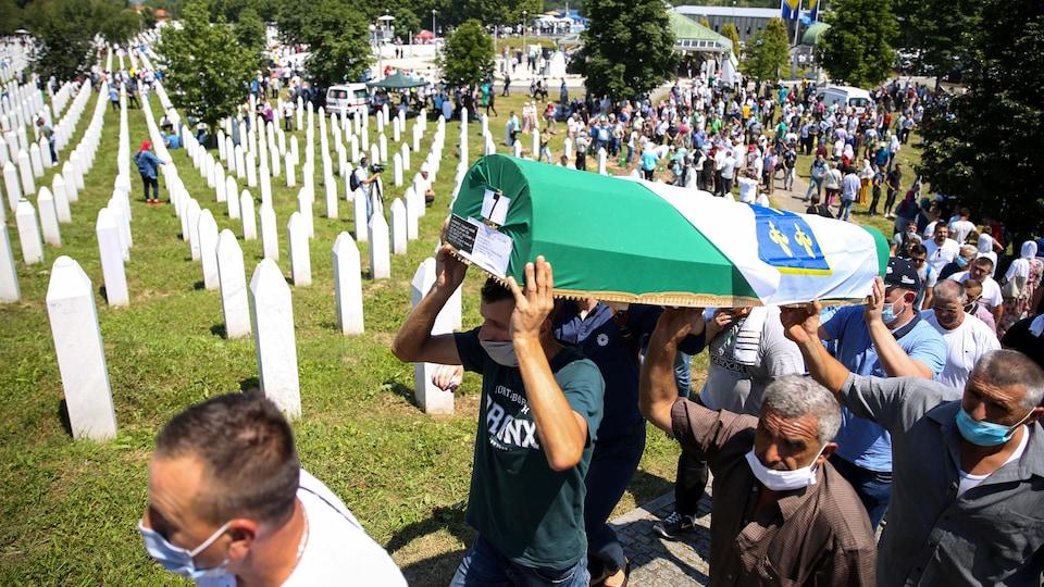 Les hommes transportent le cercueil dans le cimetière, d'autres les suivent.