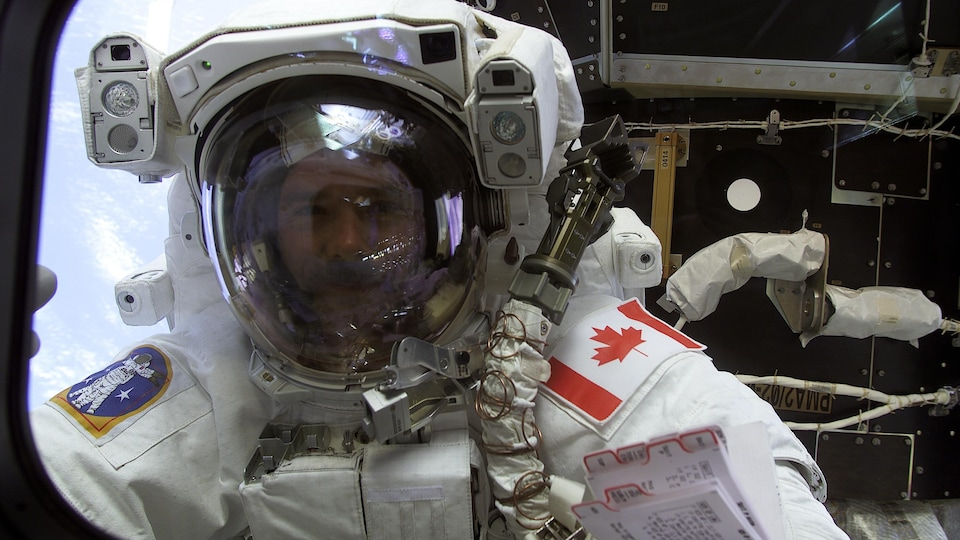 Chris Hadfield profite d'une courte pause pour jeter un coup d'oeil à travers un hublot de la navette Endeavour.
