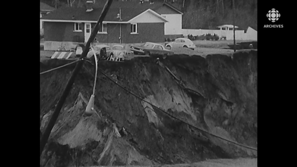 Des voitures et une maison menaçant de glisser dans le précipice dans lequel s'enfonce un poteau électrique.
