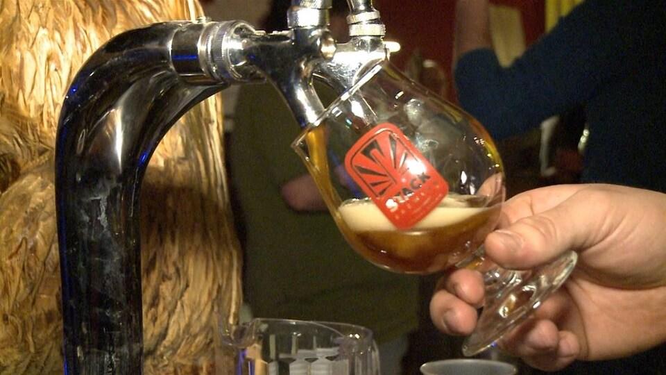 Un verre de bière se faisant remplir.