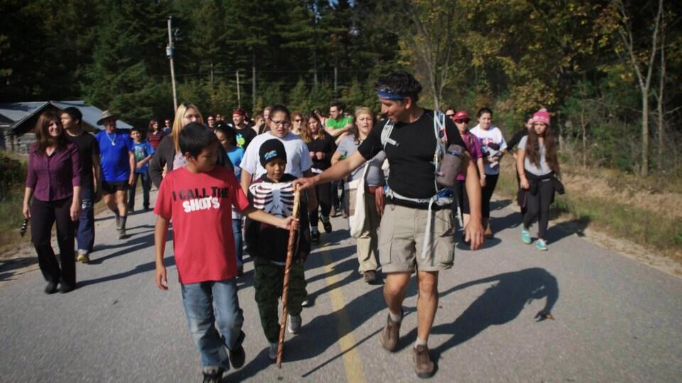 Stanley Vollant poursuit sa marche entouré d'un groupe d'enfants Innus