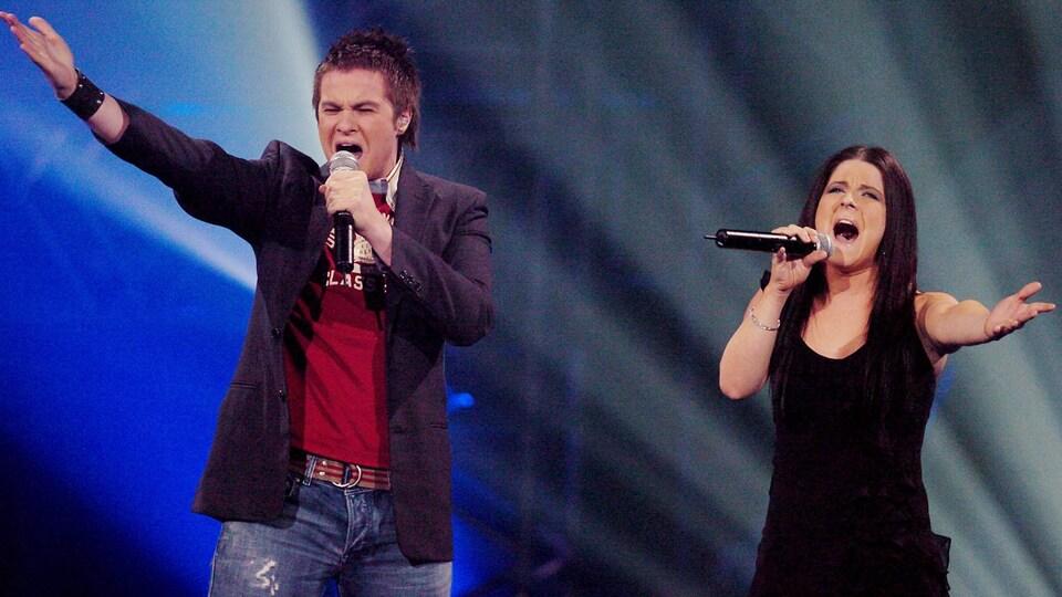 Les deux interprètes chantent dans un micro.