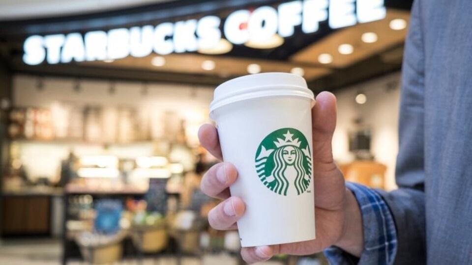 Une tasse réutilisable de Starbucks dans la main d'un client.