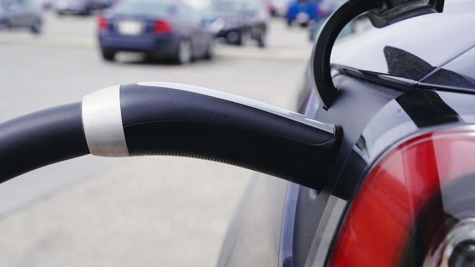 Une prise de recharge Tesla branchée sur une voiture.