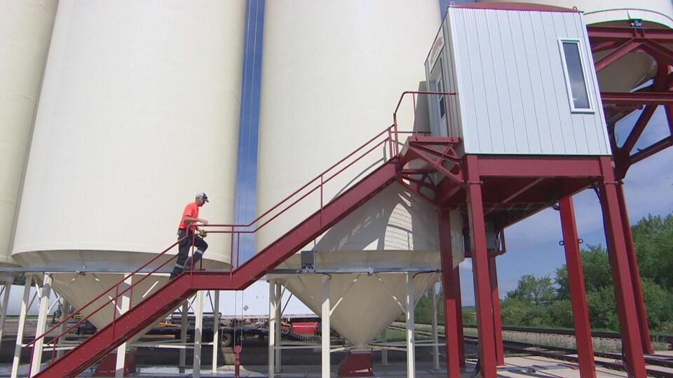 Les grands silos blancs. Au premier plan : un escalier rouge qui mène à la cabine de la station de chargement. Un homme monte les marches.